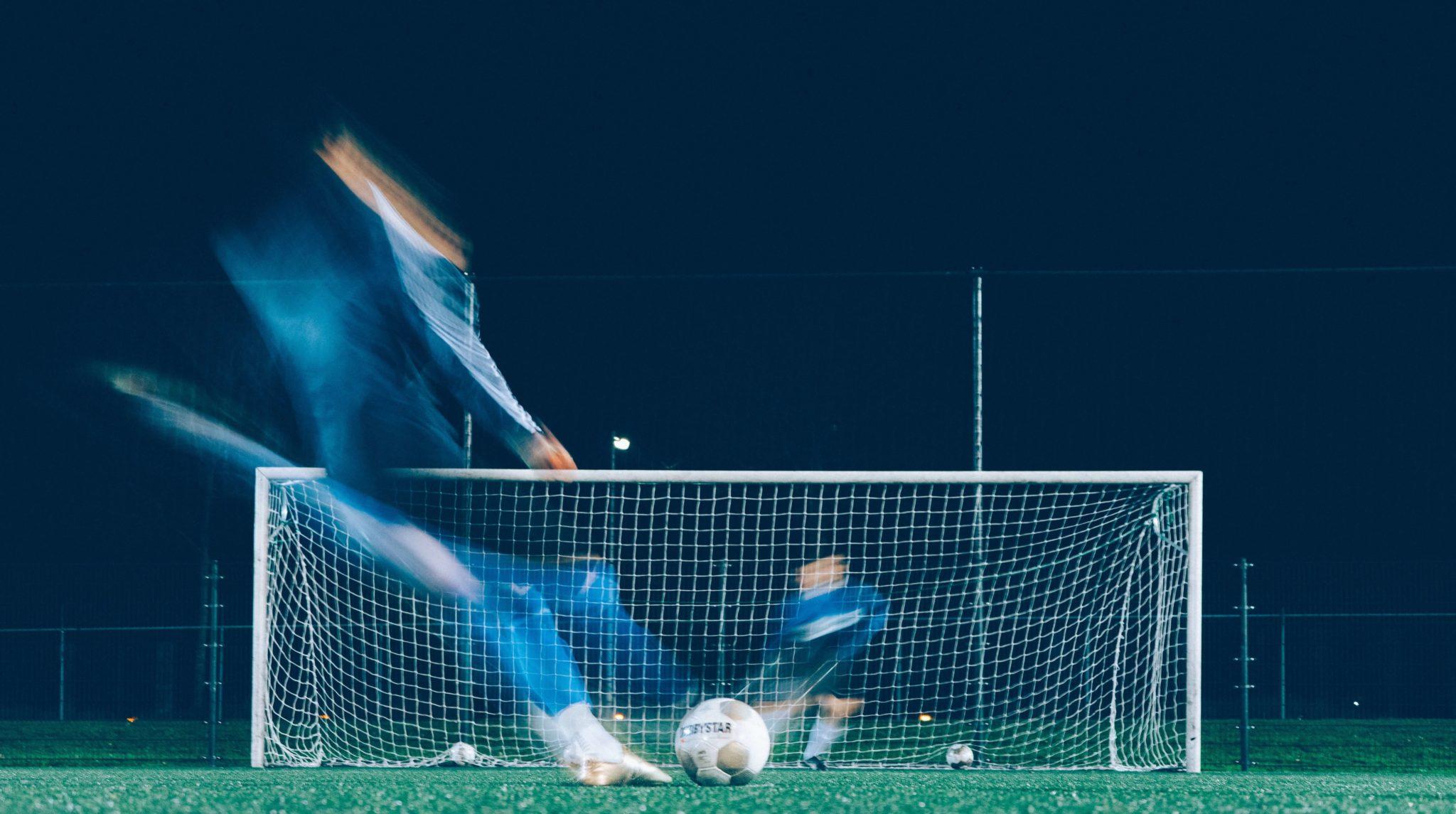 Artistic shot of footballer kicking ball towards goal and goalkeeper